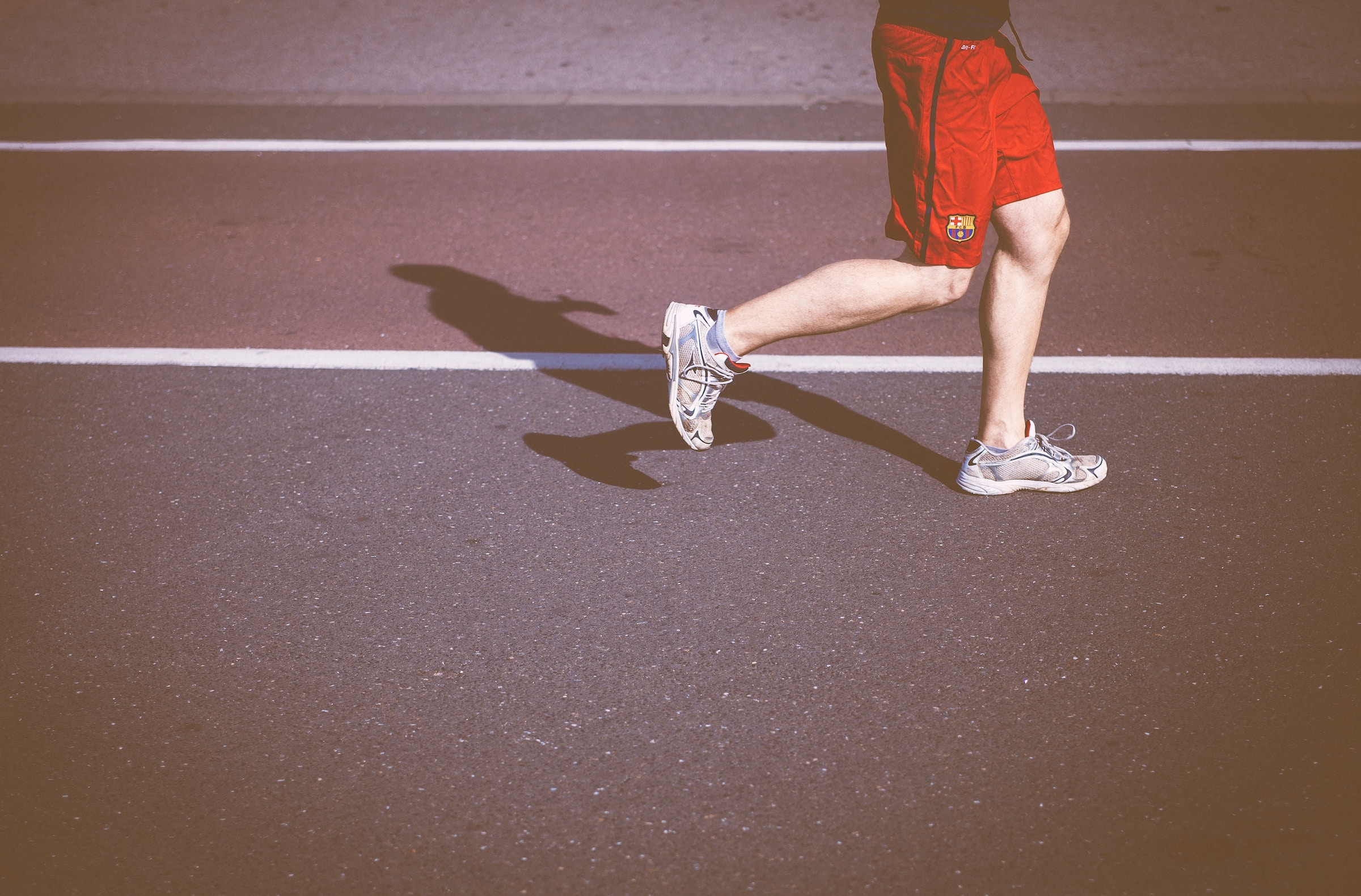 Man in red shorts running on a track